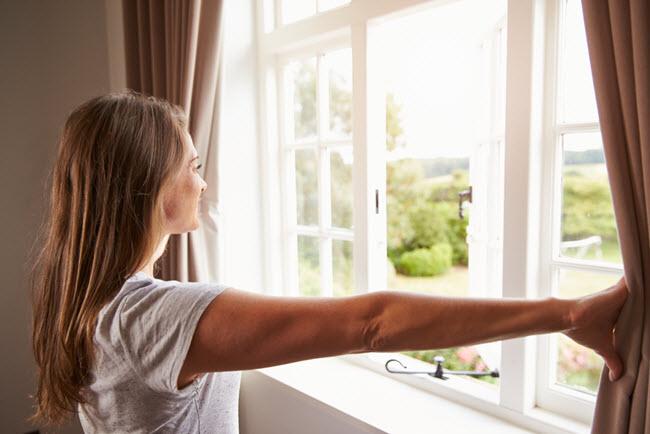 woman opening window